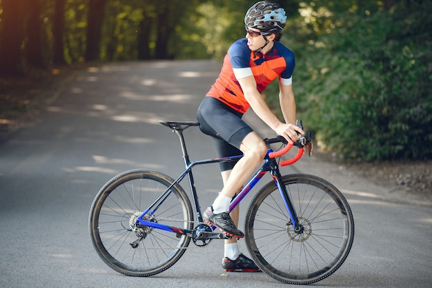 Sportowy mężczyzna jedzie rower w lato lesie