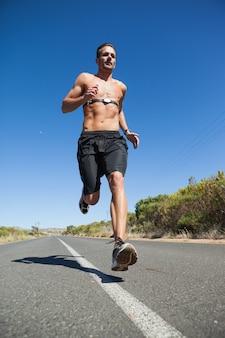 Sportowy mężczyzna jogging na otwartej drodze z monitorem wokoło klatki piersiowej