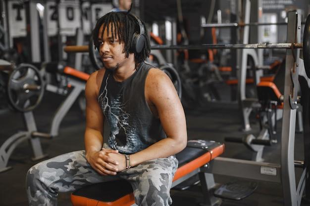 Sportowy mężczyzna na siłowni. murzyn wykonuje ćwiczenia. facet w czarnej koszulce