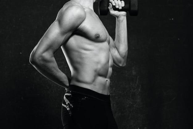 Sportowy mężczyzna nagi tors napompowane ciało pozowanie ciemne tło