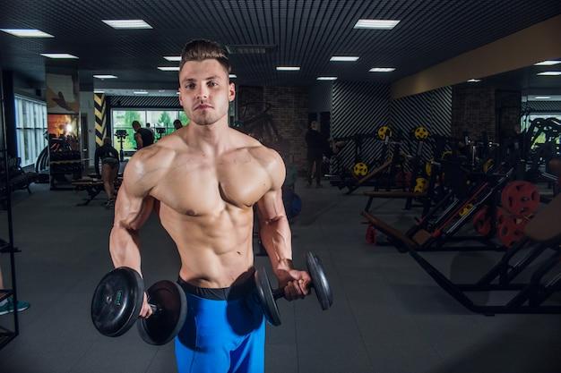 Sportowy mężczyzna o dużych mięśniach i szerokim plecach trenujący na siłowni