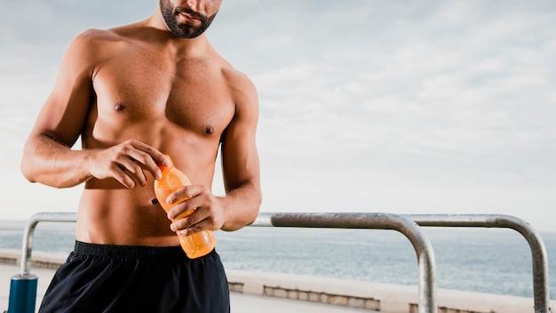 Sportowy mężczyzna pije, aby nawodnić się po treningu