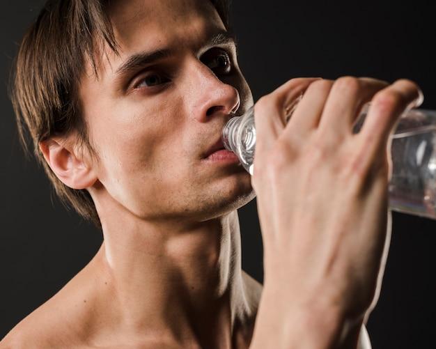 Sportowy mężczyzna pije wodę z butelki