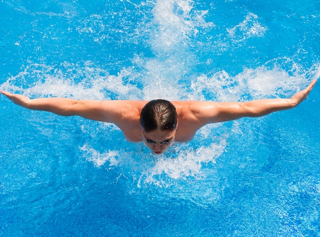 Sportowy mężczyzna pływanie w stylu motyla basenu