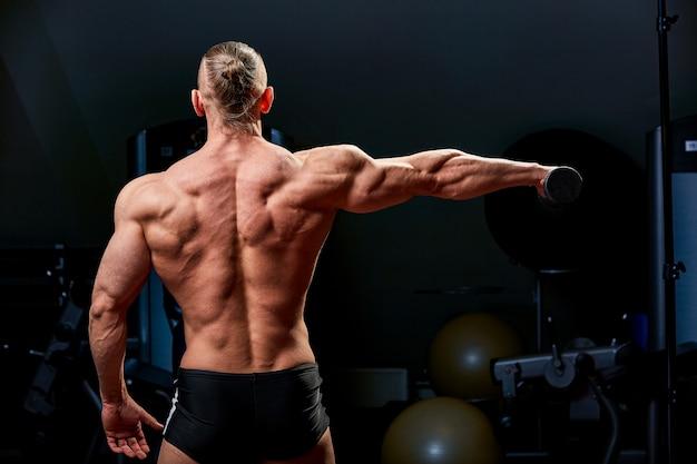 Sportowy mężczyzna pozowanie. fotografia mężczyzna z doskonałą budową ciała na czerni ścianie. widok z tyłu. siła i motywacja