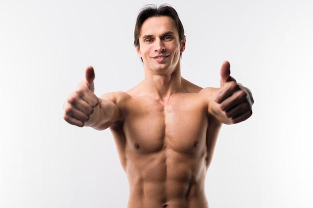Sportowy mężczyzna pozuje bez koszuli i daje aprobatom