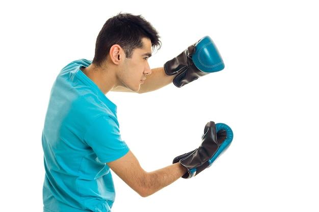 Sportowy mężczyzna pozuje w niebieskiej koszuli i rękawicach bokserskich na białym tle w studio