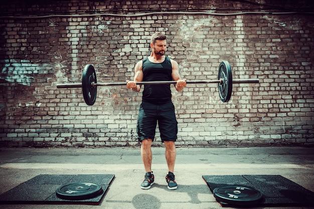 Sportowy mężczyzna pracujący z sztangą. siła i motywacja. ćwiczenie bicepsa.