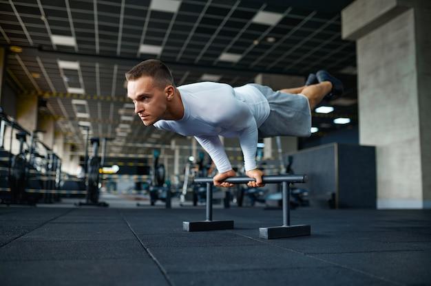 Sportowy mężczyzna robi ćwiczenia abs, trening fitness w siłowni