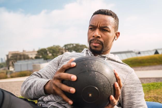 Sportowy mężczyzna robi ćwiczeniu z medycyny piłką.