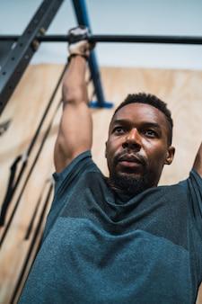 Sportowy mężczyzna robi pull up ćwiczeniu przy gym.
