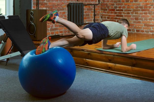 Sportowy mężczyzna robi równoważenia ćwiczeniom z gym piłką