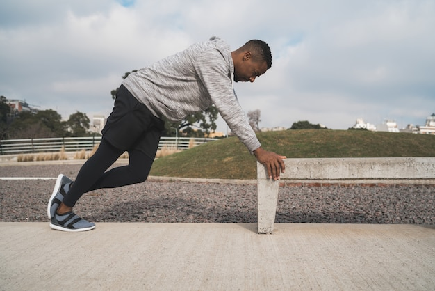 Sportowy mężczyzna rozciąganie przed ćwiczeniem.