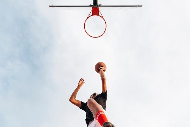Sportowy mężczyzna rzuca koszykówkę w sieć