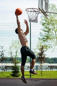Sportowy mężczyzna rzuca piłkę do obręczy