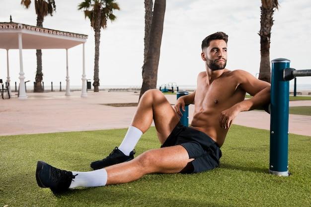 Sportowy mężczyzna siedzi na trawie po uruchomieniu