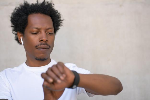Sportowy mężczyzna sprawdzanie czasu na swoim inteligentnym zegarku podczas ćwiczeń na świeżym powietrzu. pojęcie sportu i zdrowego stylu życia.