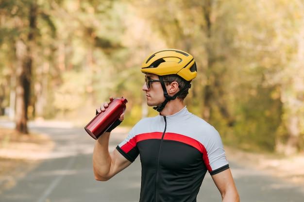 Sportowy mężczyzna stoi na drodze z rowerem