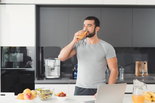 Sportowy mężczyzna stoi w kuchni i pije sok pomarańczowy.