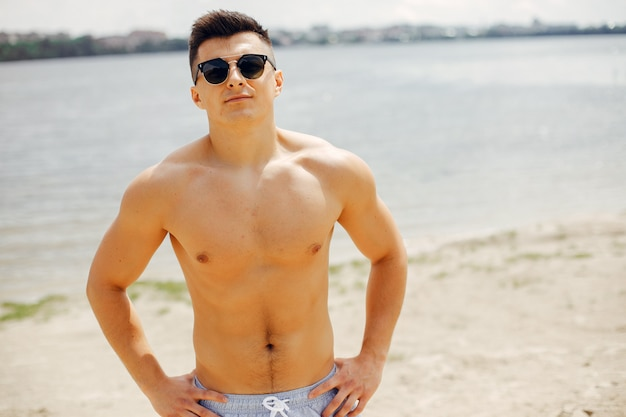 Sportowy mężczyzna trenuje na plaży