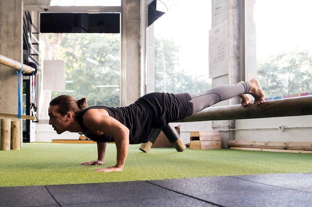 Sportowy mężczyzna trenuje na siłowni, robiąc pompki