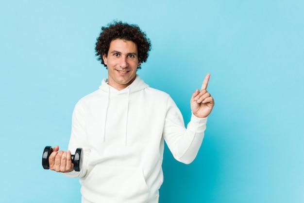 Sportowy mężczyzna trzyma hantle uśmiecha się wesoło wskazując palcem wskazującym daleko