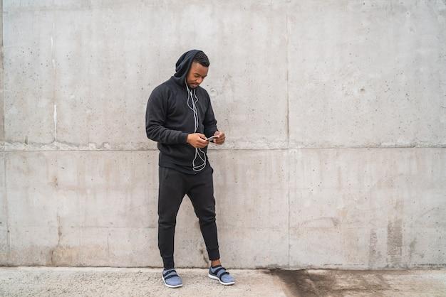Sportowy mężczyzna używa jego telefon.