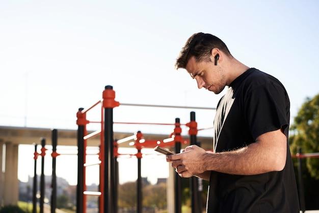 Sportowy mężczyzna w barze przy użyciu swojego smartfona podczas treningu kalisteniki na świeżym powietrzu.