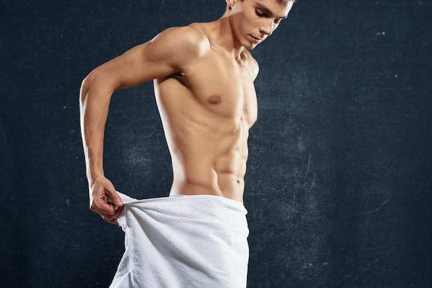 Sportowy mężczyzna w białych spodenkach treningu fitness ciemnym tle