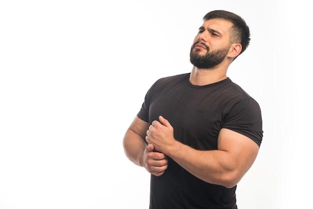 Sportowy mężczyzna w czarnej koszuli demonstrujący mięśnie ramion.