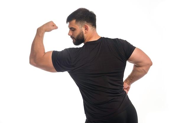 Sportowy mężczyzna w czarnej koszuli pokazując mięśnie bicepsów.