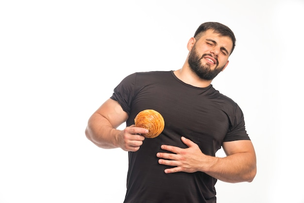 Sportowy mężczyzna w czarnej koszuli pokazujący pączka i trzyma się za brzuch.