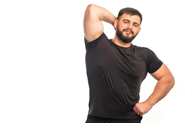 Sportowy mężczyzna w czarnej koszuli pokazuje jego mięsień triceps.
