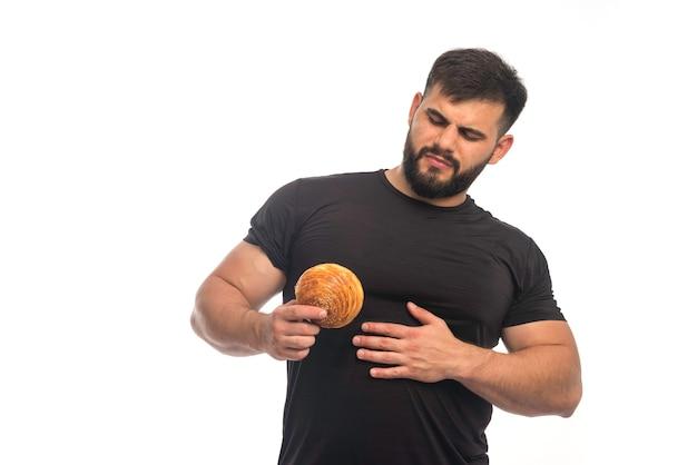Sportowy mężczyzna w czarnej koszuli pokazuje pączka i trzyma się za brzuch