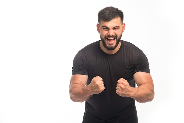 Sportowy mężczyzna w czarnej koszuli pokazuje swoje tricepsy i wrzeszczy.