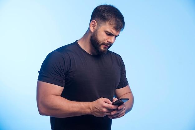 Sportowy mężczyzna w czarnej koszuli trzyma telefon i sms-y.
