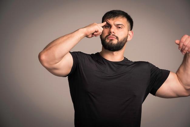 Sportowy mężczyzna w czarnej koszuli wygląda zamyślony.