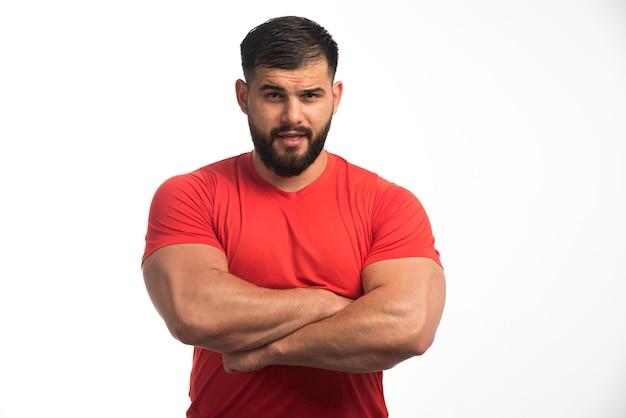 Sportowy mężczyzna w czerwonej koszuli demonstrujący swoje górne mięśnie.