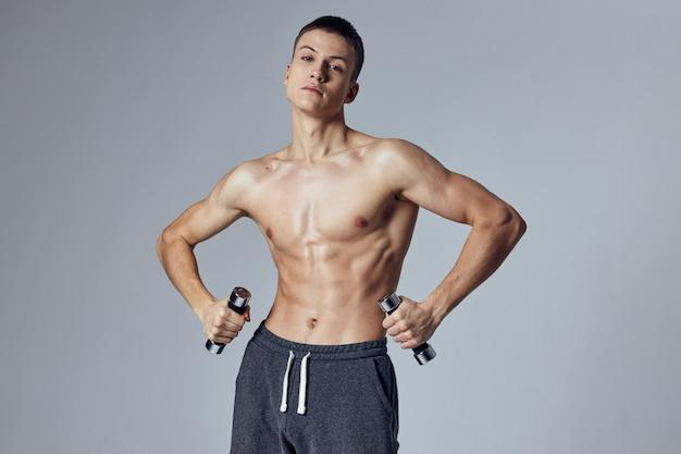 Sportowy mężczyzna w krótkich spodenkach z hantlami w rękach ćwiczenia treningowe.