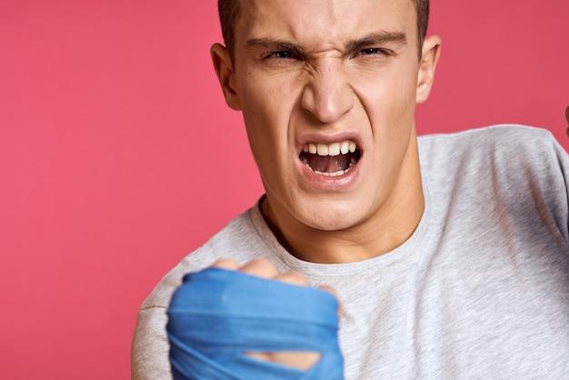 Sportowy mężczyzna w niebieskich rękawicach bokserskich i koszulce na różowym tle ćwiczy uderzenia pięścią przycięty widok