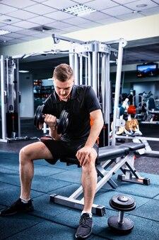 Sportowy mężczyzna w odzieży sportowej podnoszący ciężary i pracujący na bicepsach na siłowni