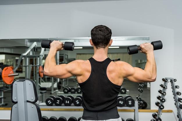 Sportowy mężczyzna w siłowni z hantlami
