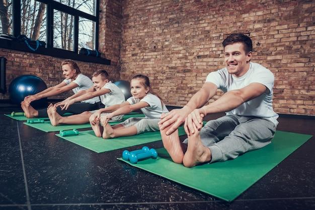 Sportowy mężczyzna w siłowni ze szczęśliwą rodziną.