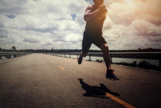 Sportowy mężczyzna z biegaczem na ulicie biegał dla ćwiczenia