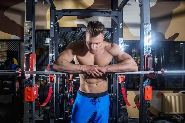 Sportowy mężczyzna z dużymi mięśniami i szerokimi plecami trenuje na siłowni, fitnessie i napompowanej prasie brzusznej.