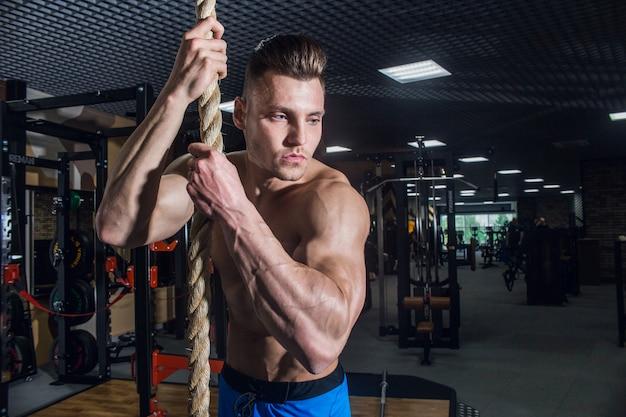 Sportowy mężczyzna z dużymi mięśniami i szerokimi plecami trenuje na siłowni, fitnessie i napompowanej prasie brzusznej