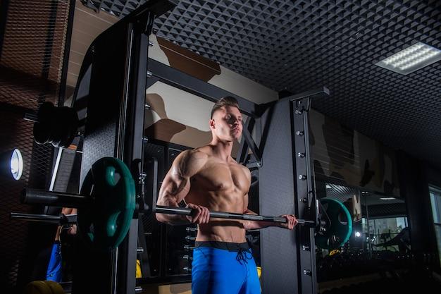 Sportowy mężczyzna z dużymi mięśniami i szerokimi plecami trenuje na siłowni