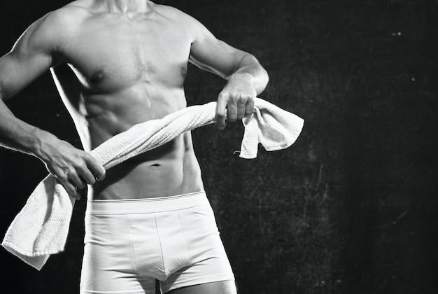 Sportowy mężczyzna z napompowanym ciałem ciemnym tle