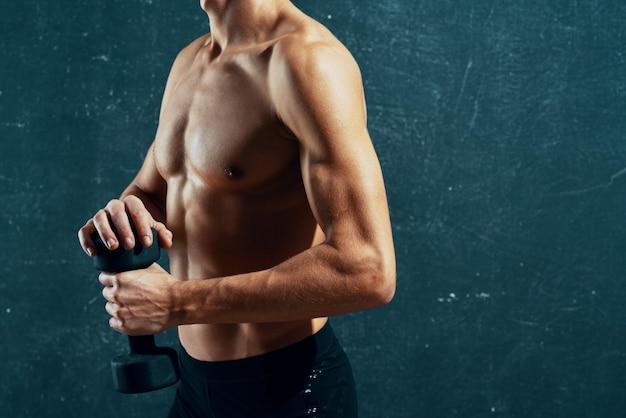 Sportowy mężczyzna z napompowanym treningiem ciała ćwiczy ciemne tło