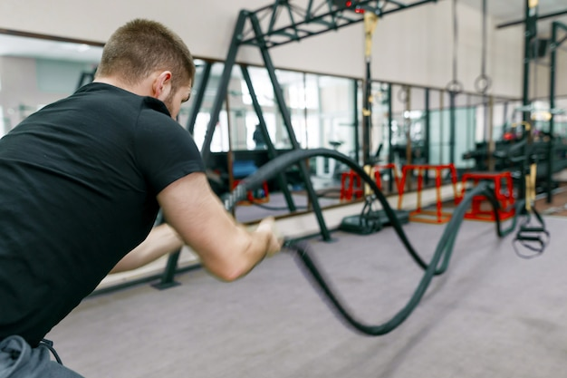 Sportowy mięśni brodaty mężczyzna ćwiczy w gym